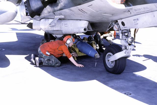 A bomb loader is used to lift and secure a bomb into position beneath an AV-8A Harrier aircraft aboard the amphibious assault ship USS NASSAU (LHA-4)