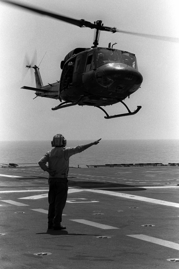 A flight deck crewman gives signals as a UH-1N Iroquois helicopter from Marine Medium Helicopter Squadron 265 (HMM-265) prepares to land aboard the amphibious assault ship USS TRIPOLI (LPH-10) during exercise Team Spirit '82