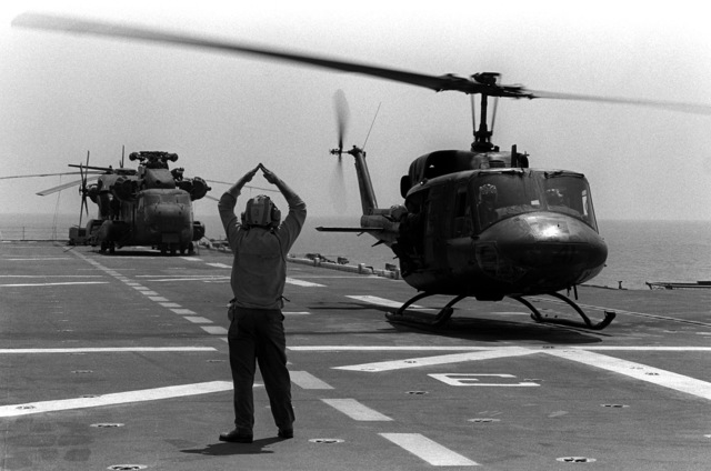 A flight deck crewman signals to a UH-1N Iroquois helicopter landing aboard the amphibious assault ship USS TRIPOLI (LPH-10) during exercise Team Spirit '82. The helicopter is from Marine Medium Helicopter Squadron 265 (HMM-265)