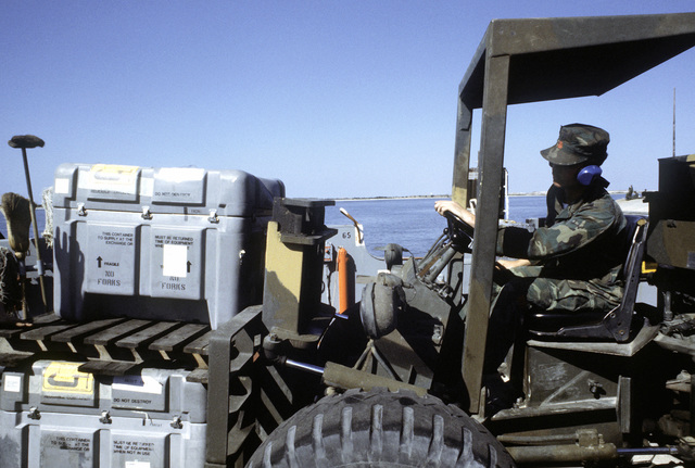 A forklift is used to load supplies aboard the Utility Landing Craft 1662 (LCU-1662)