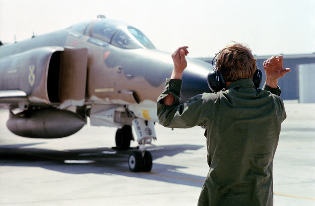 A ground crewman from the 37th Tactical Fighter Wing guides an F-4 Phantom II aircraft onto the runway apron during Exercise Gallant Eagle '82