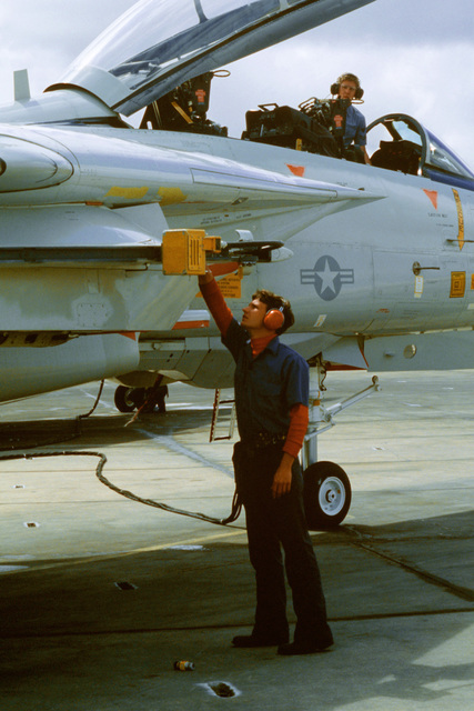 A ground crewman uses a Release Control Check Box to check the release mechanism on the bomb and rocket rail of an F-14 Tomcat aircraft during Exercise Gallant Eagle '82