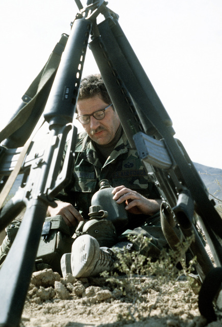 A member of the 82nd Airborne Division is seen through stacked M-16A1 rifles as he takes a drink from his canteen at the end of a day of combat exercises taking place during Exercise Gallant Eagle '82