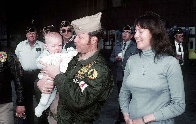 A Navy pilot from Light Attack Squadron 27 (VA-27) greets his son upon his return from a Western Pacific deployment aboard the aircraft carrier USS CORAL SEA (CV-43)