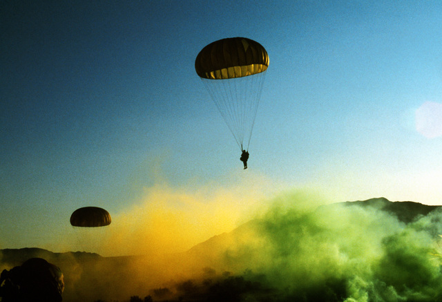 A paratrooper from the 82nd Airborne Division descends into a smoke screen after his jump from a C-130 Hercules aircraft during Exercise Gallant Eagle