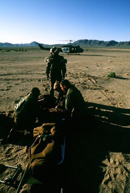 A paratrooper from the 82nd Airborne Division is prepared for medical evacuation (medevac) aboard a UH-1 Iroquois helicopter. The paratrooper was injured in a jump from a C-130 Hercules aircraft during Exercise Gallant Eagle