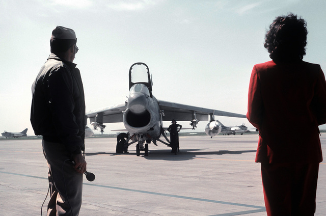 A public affairs officer waits to welcome Navy pilots from Carrier Air Wing 14 (CVW-14) home after a Western Pacific deployment aboard the aircraft carrier USS CORAL SEA (CV-43). A wife of one of the pilots is standing on the right