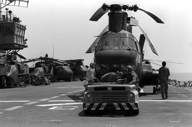 A tow tractor prepares to move a Marine CH-46 Sea Knight helicopter from Marine Medium Helicopter Squadron 265 (HMM-265) on the flight deck of the amphibious assault ship USS TRIPOLI (LPH-10). The TRIPOLI is participating in exercise Team Spirit '82