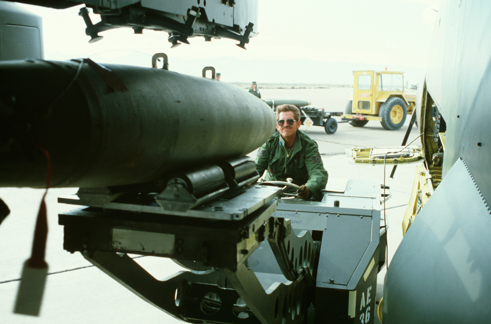 A weapons technician operates a bomb loader to upload a bomb onto the wing pylon of an A-7D Corsair II aircraft during Exercise Gallant Eagle '82