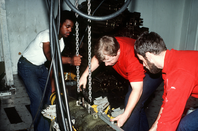 AIRMAN recruit Reginald D. Johnson, left, and two ordnancemen load a Mark 82 bomb on a bomb skid aboard the aircraft carrier USS JOHN F. KENNEDY (CV-67)