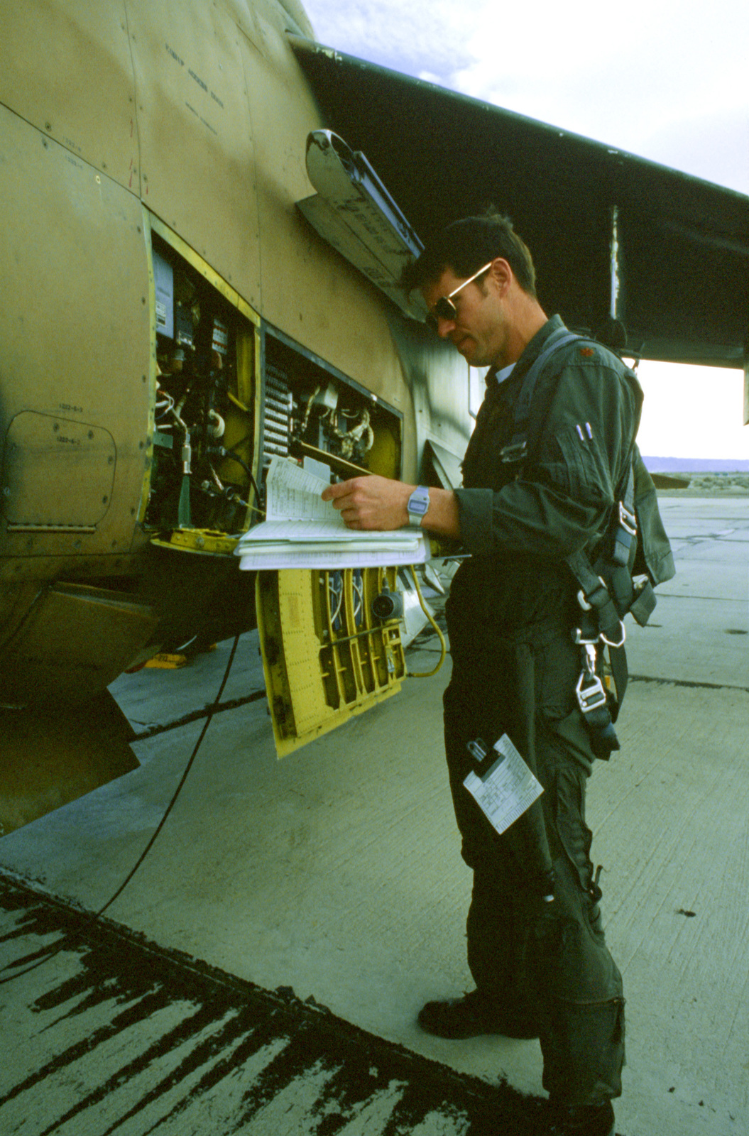An A-7D Corsair II aircraft pilot reads maintenance forms while he inspects his aircraft during Exercise Gallant Eagle '82
