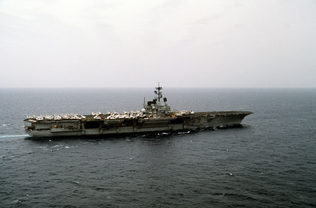 An aerial starboard beam view of the aircraft carrier USS FORRESTAL (CV-59) underway