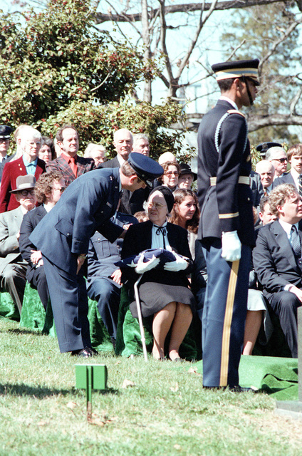 An Air Force officer speaks to a family member at the full honors funeral for GEN Nathan Twining, chairman of the Joint Chiefs of STAFF from 1957-1960, at the Arlington National Cemetery