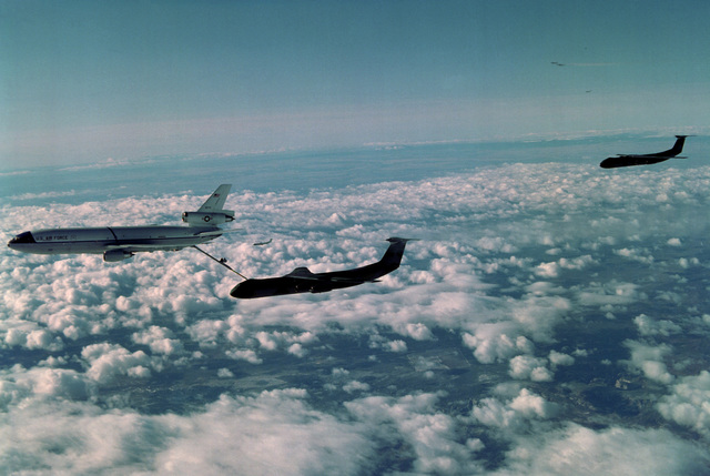 An air-to-air left side view of a KC-10 Extender aircraft refueling a C-141 Starlifter aircraft as they return from a mass troop and equipment drop over Fort Irwin during exercise Gallant Eagle '82