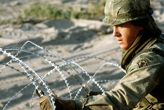 """An Army combat engineers strings concertina wire along the front line to stop """"aggressor forces"""" during Exercise Gallant Eagle '82"""