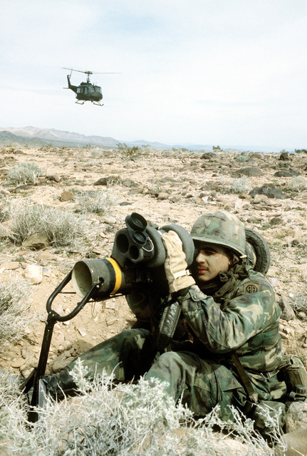 """An UH-1 Iroquois helicopter lands to provide air support, while an infantryman aims his anti-tank weapon toward the """"enemy"""" during Exercise Gallant Eagle '82"""