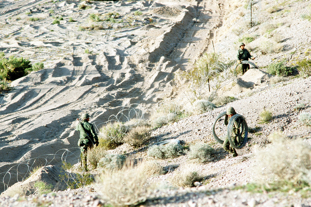 """Army combat engineers string concertina wire along the front line, to stop """"aggressor forces"""" during Exercise Gallant Eagle '82"""