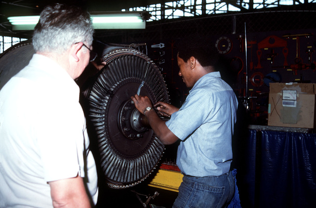 Aviation Machinist's Mate 2nd Class (AD2) Floyd Kirksey and civilian employee Don Borden perform maintenance on a J57 turbine engine
