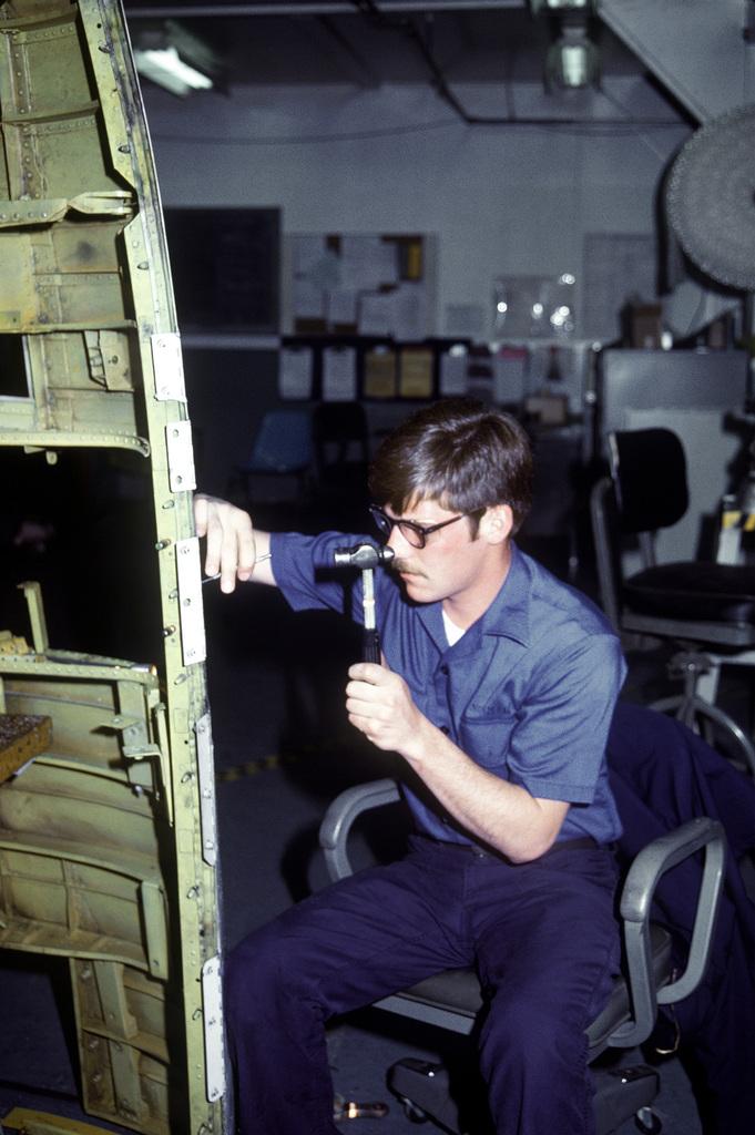 Aviation Structural Mechanic AMN Ernie Schmidt works on an A-7 Corsair II aircraft belly pan