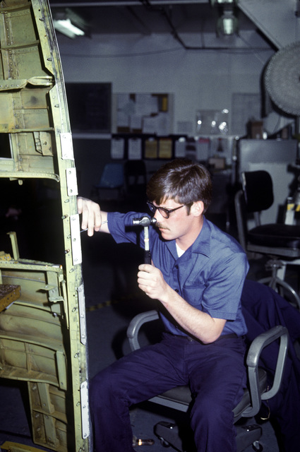 Aviation Structural Mechanic AMN Ernie Schmidt works on an A-7 Corsair II aircraft belly pan