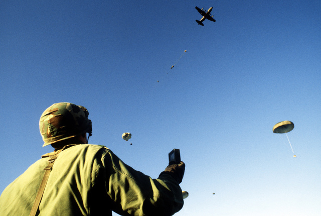 CPT Jim Danley, 82nd Airborne Division uses a meter to check the wind direction as cargo is dropped from a C-130 Hercules aircraft during Exercise Gallant Eagle