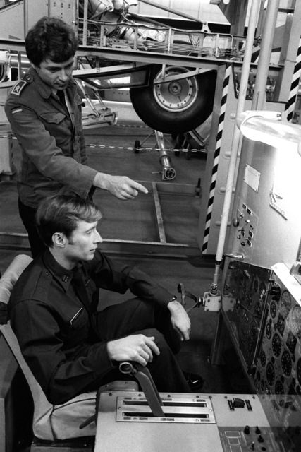 CPT Richard Peters operates a C-160 Transall aircraft hydraulics simulator, as German Air Force MSGT Franz Kandler points out the meaning of the various gauges, during a training course on the aircraft's operation. The Transall is a joint German-French design which serves as the primary strategic tactical support for the Germany Air Force