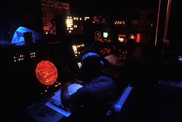 Crewmen monitor radar scopes in the combat information center aboard the amphibious assault ship USS NASSAU (LHA-4)