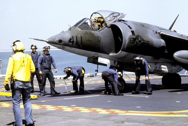 Flight deck crewmen aboard the amphibious assault ship USS NASSAU (LHA-4) prepare an AV-8 Harrier aircraft for flight