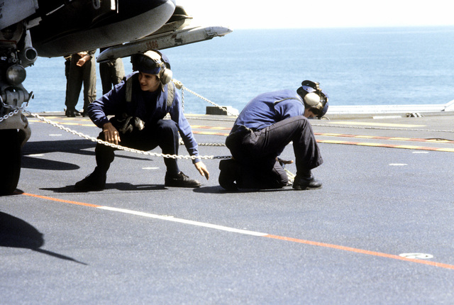 Flight deck crewmen loosen the tie-down chains as they prepare an aircraft for take-off from the amphibious assault ship USS NASSAU (LHA-4)