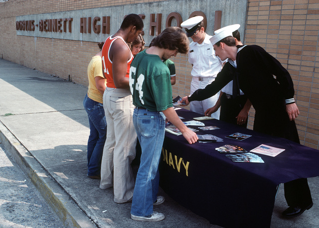 From right to left, SA David Mintz, EW2 Mike Cornett and SN Mark Powers participate in the Hometown Assistant to Recruiting Program (HARP) by handing out information brochures and answering questions from high school students