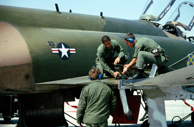 Ground crewmen from the 37th Tactical Fighter Wing perform maintenance on an F-4 Phantom II aircraft during Exercise Gallant Eagle '82