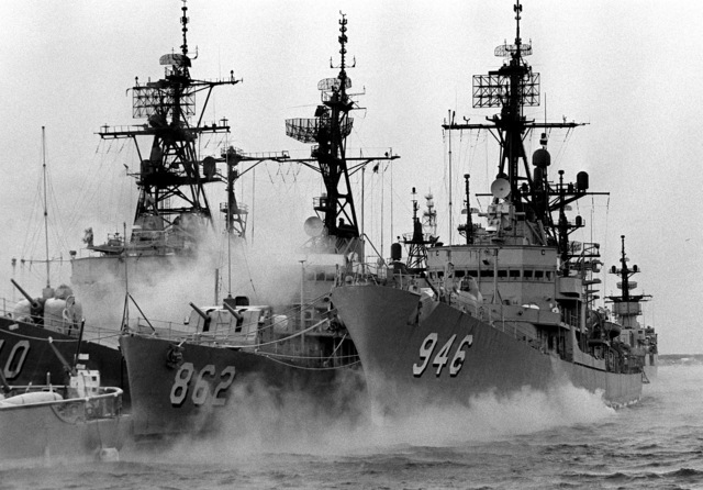 Mist surrounds three docked destroyers. The destroyers are, from left to right: the USS MANLEY (DD-940), the USS VOGELGESANG (DD-862) and the USS EDSON (DD-946)