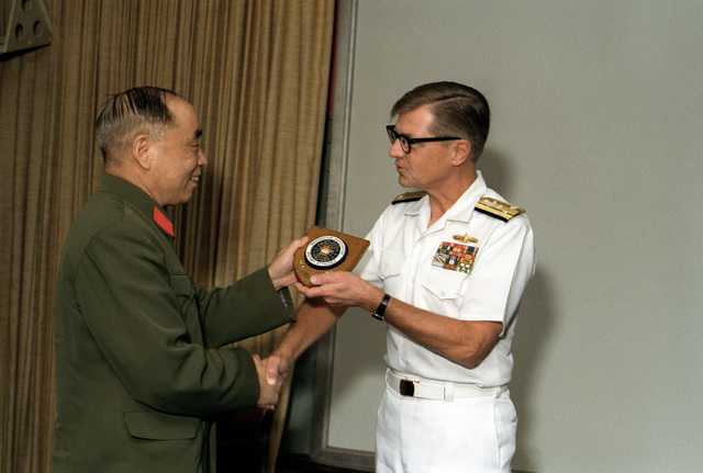 Mr. Xu Yimin, Defense and Military Attache, People's Republic of China, left, presents VADM Edward S. Briggs, deputy and chief of staff, with a plaque during a briefing at Pacific Fleet headquarters