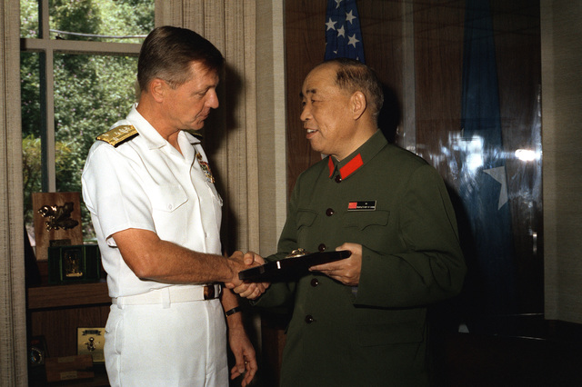 Mr. Xu Yimin, right, Defense and Military Attache, People's Republic of China, accepts a plaque from VADM Edward S. Briggs, deputy and chief of staff, while visiting his office at headquarters U.S. Pacific Fleet