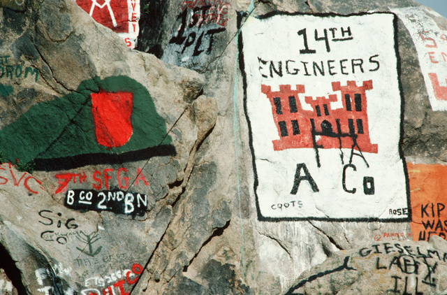 Organizational emblems and symbols appear on a rock formation outside the main entrance, displaying some of the units that are participating in exercise Gallant Eagle '82