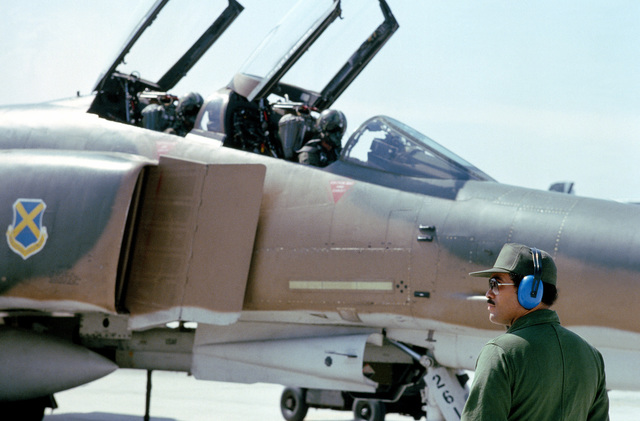 Pilots from the 37th Tactical Fighter Wing conduct a preflight check of an F-4 Phantom II aircraft during Exercise Gallant Eagle '82