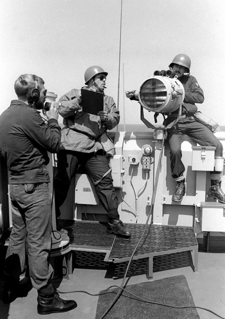 Signalman 3rd Class (SM3) Steve Woods, using a signal searchlight, SM2 Ron Lindgren, using sound powered phones, and SM1 Mike Tullgren, center, practice sending messages from the tank landing ship USS FRESNO (LST-1182) to the dock landing ship USS MOUNT VERNON (LSD-39) during exercise Team Spirit '82