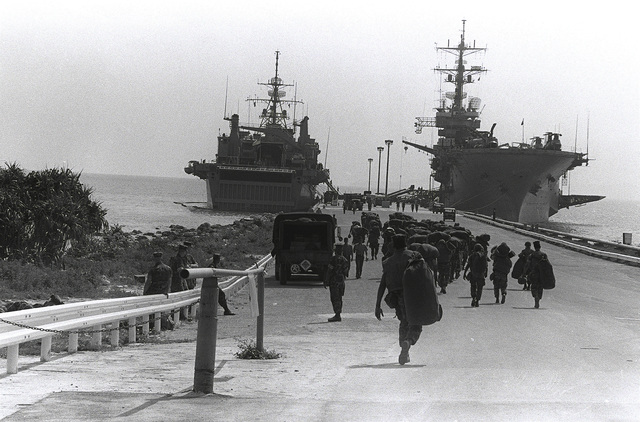 U.S. Marines walk down to the pier to board the amphibious assault ship USS TRIPOLI (LPH-10), right, and the amphibious transport dock USS DUBUQUE (LPD-8) to participate in exercise Team Spirit '82