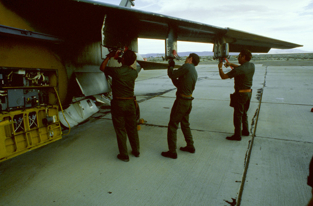 Weapons technicians prepare an A-7D Corsair II aircraft for the uploading of 500-pound bombs during Exercise Gallant Eagle '82