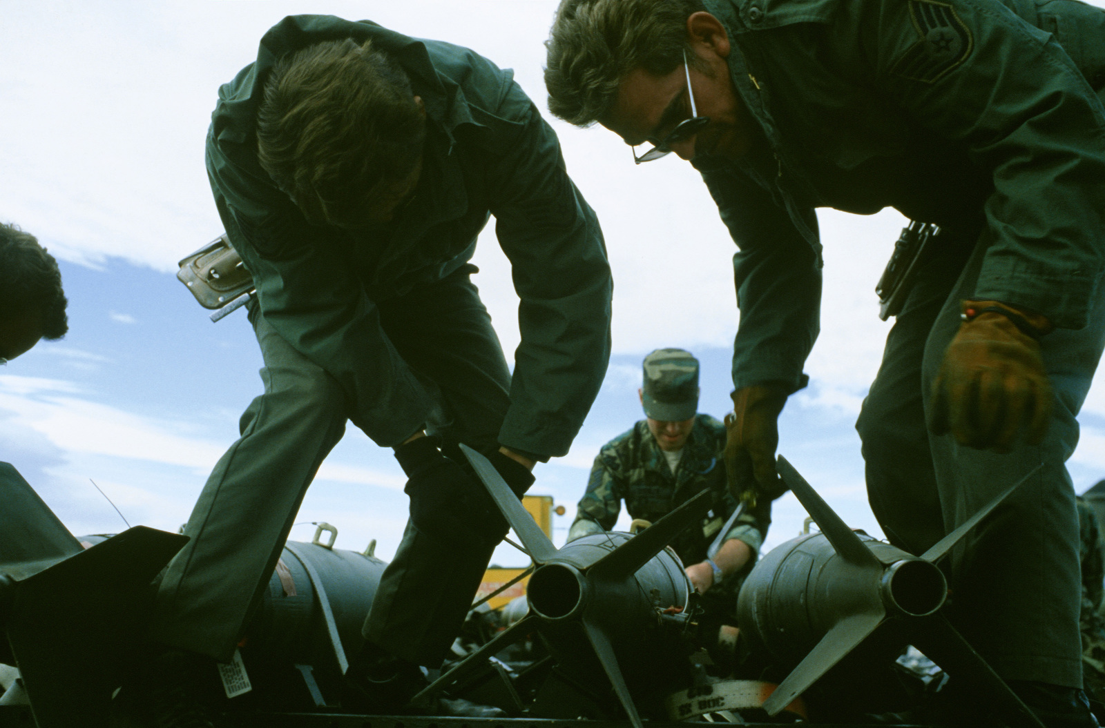 Weapons technicians prepare to upload bombs onto an A-7D Corsair II aircraft during Exercise Gallant Eagle '82