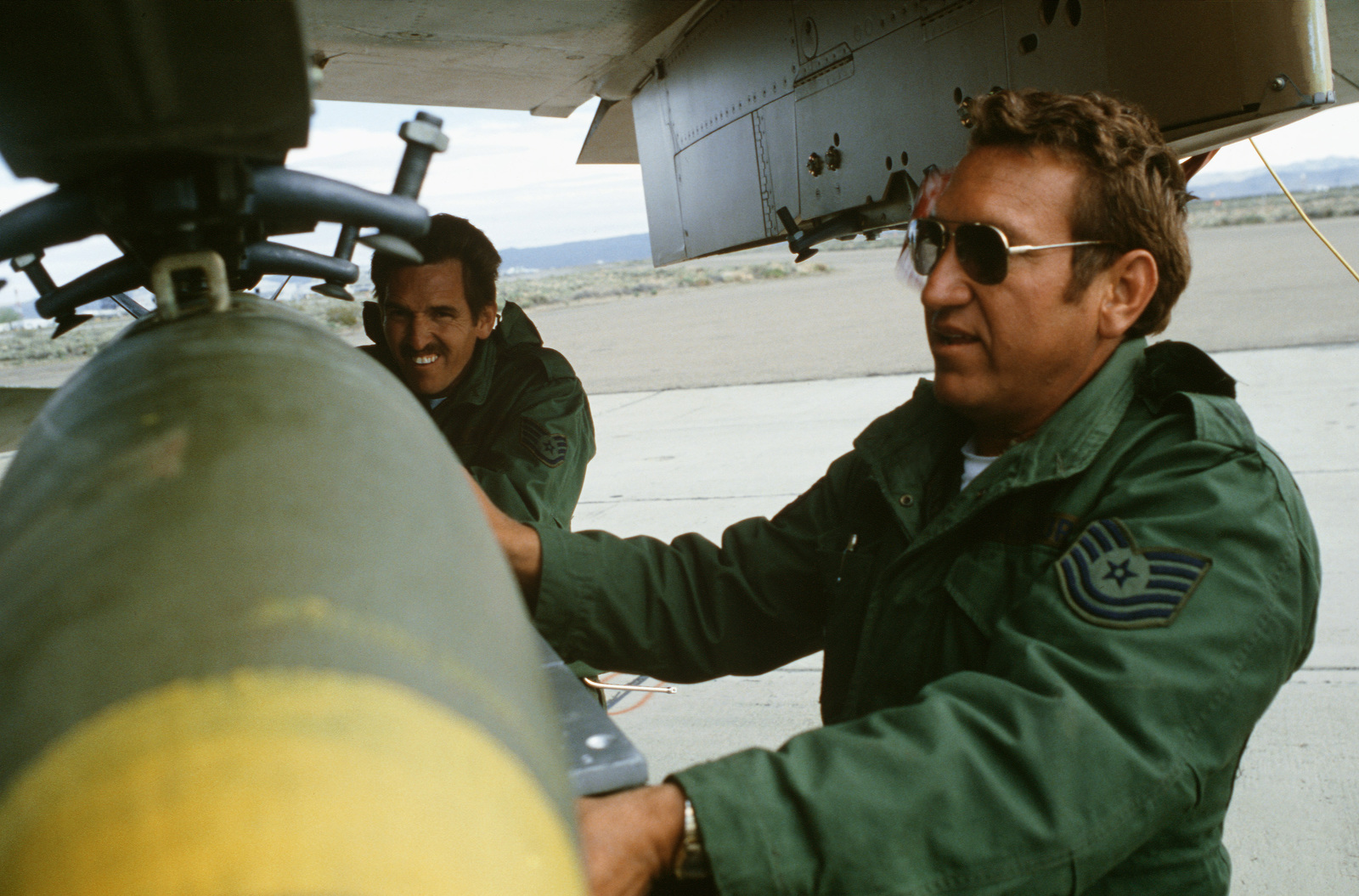 Weapons technicians upload a bomb onto the wing pylon of an A-7D Corsair II aircraft during Exercise Gallant Eagle '82