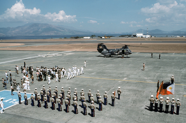 Navy sideboys move toward the CH-46A Sea Knight helicopter from Helicopter Combat Support Squadron 11 (HC-11) to welcome Secretary of Defense Caspar W. Weinberger to Arthur W. Radford Field for a visit