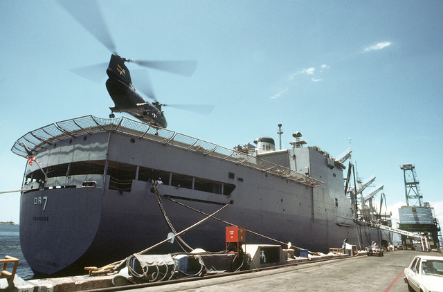 Secretary of Defense Caspar W. Weinberger, aboard a CH-46A Sea Knight helicopter from Helicopter Combat Support Squadron 11 (HC-11), prepares to land on the stern of the USS ROANOKE (AOR-7) for a tour of the replenishment oiler