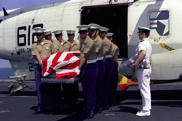 U.S. Marines aboard the aircraft carrier USS INDEPENDENCE (CV-62) offload the remains of Lieutenant Commander Nicholas George Brooks from an SH-3 Sea King helicopter, attached to Carrier Air Wing 6 (CVW-6). Brooks, killed in action over Laos in 1973, will be given a burial-at-sea service