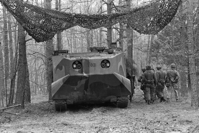 A Marine amphibious LVTC-7 tracked command vehicles that is a part of the Combined Arms Operation (CAO 1-82), is in the process of being camouflaged with a net, cut trees and branches. The Marines participating are a branches. The Marines participating are a part of the 6th Marine Amphibious Brigade