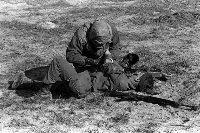 A Marine from the 6th Marine Amphibious Brigade, who is wearing an M-17A1 gas mask, gives first aid to a wounded buddy during a simulated nuclear blast. This training is a part of the Combined Arms Operation (CAO 1-82)