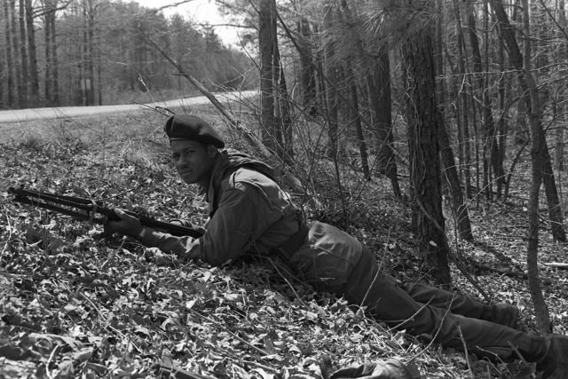 A U.S. Marine from the 6th Marine Amphibious Brigade, playing the role of an aggressor dressed as a Soviet naval infantrymen and armed with a Soviet rifle, waits in ambush during the Combined Arms Operation (CAO 1-82)