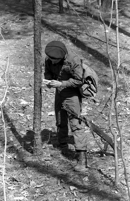 A U.S. Marine from the 6th Marine Amphibious Brigade, sets a booby trap while playing the role of an aggressor during the Combined Arms Operation (CAO 1-82). They are dressed as Soviet naval infantryman and are armed with Soviet rifles