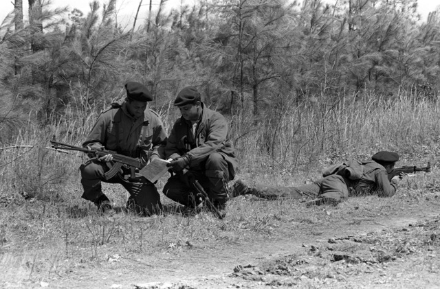 U.S. Marines from the 6th Marine Amphibious Brigade, check a map as they play the role of aggressors during the Combined Arms Operation (CAO 1-82). They are dressed as Soviet naval infantrymen and are armed with Soviet rifles