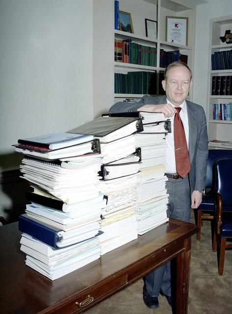 Assistant Secretary of Defense (Comptroller) Jack Borsting displays FY 83 DoD Budget paperwork prepared for Congress